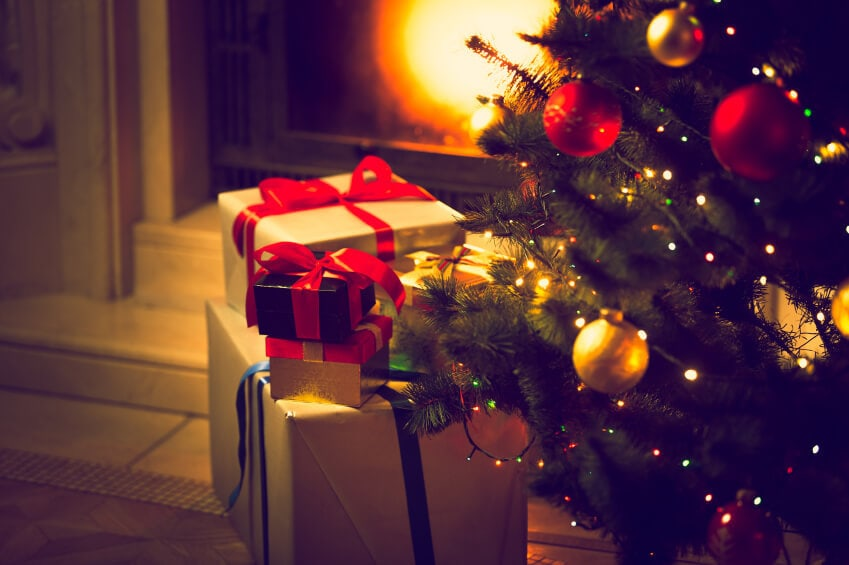 Presents and a Christmas tree by a fire