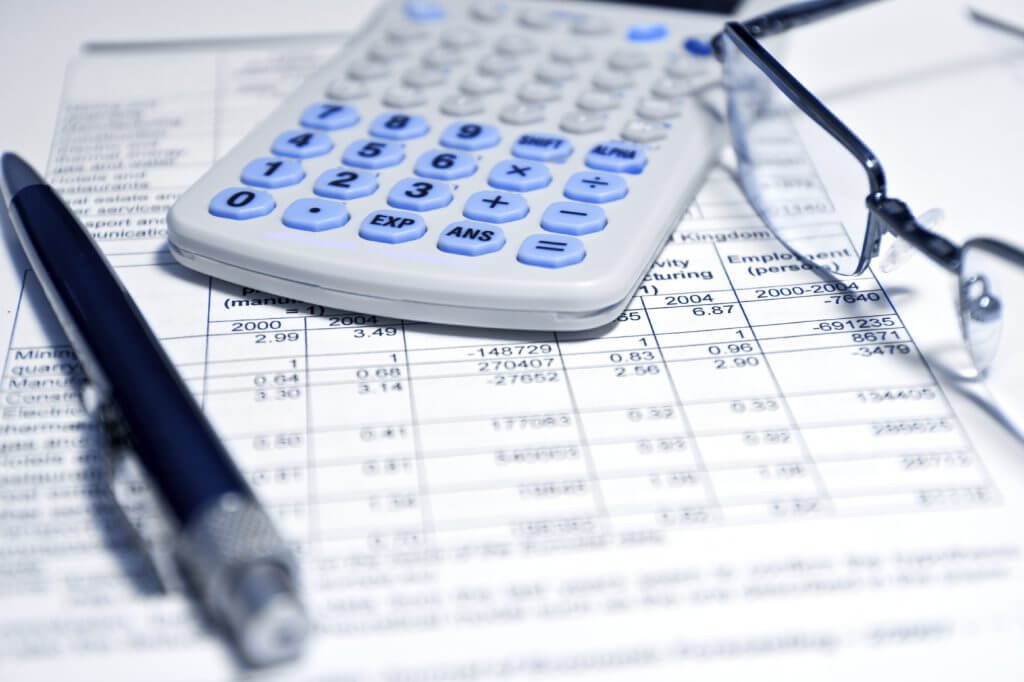 a calculator and financial paperwork helping to deal with debt
