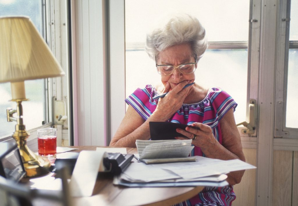 Senior woman handling finances appearing to be deep in thought