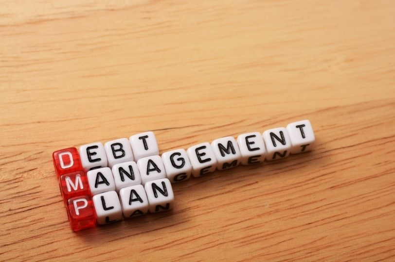 letter cubes spelling out 'debt management plan' on a wooden table