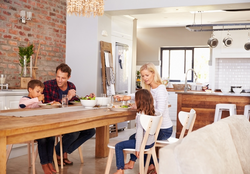 family cooking a meal at home to save money for a holiday