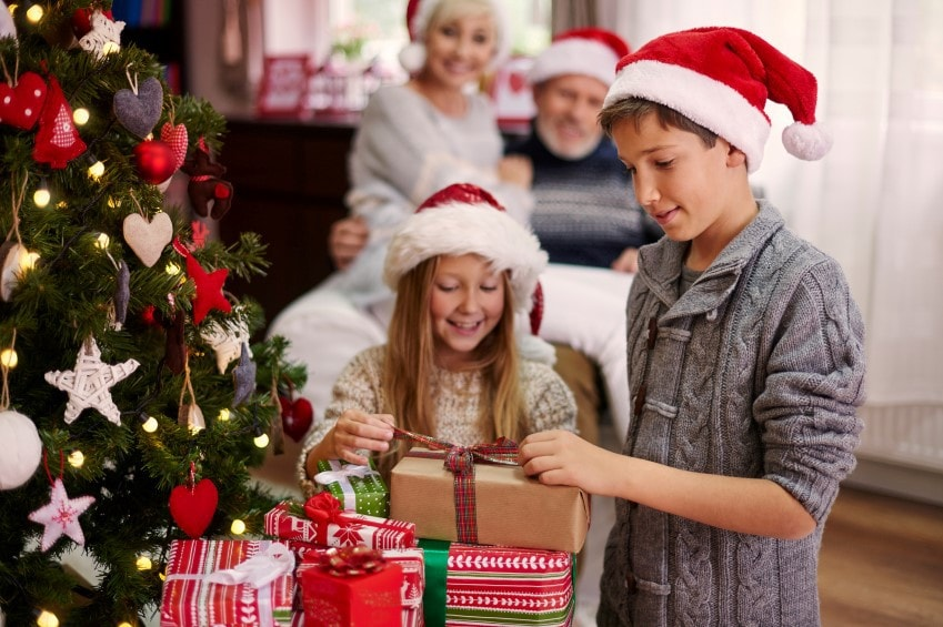young brother ans sister observing presents under a Christmas tree while wearing Christmas hats