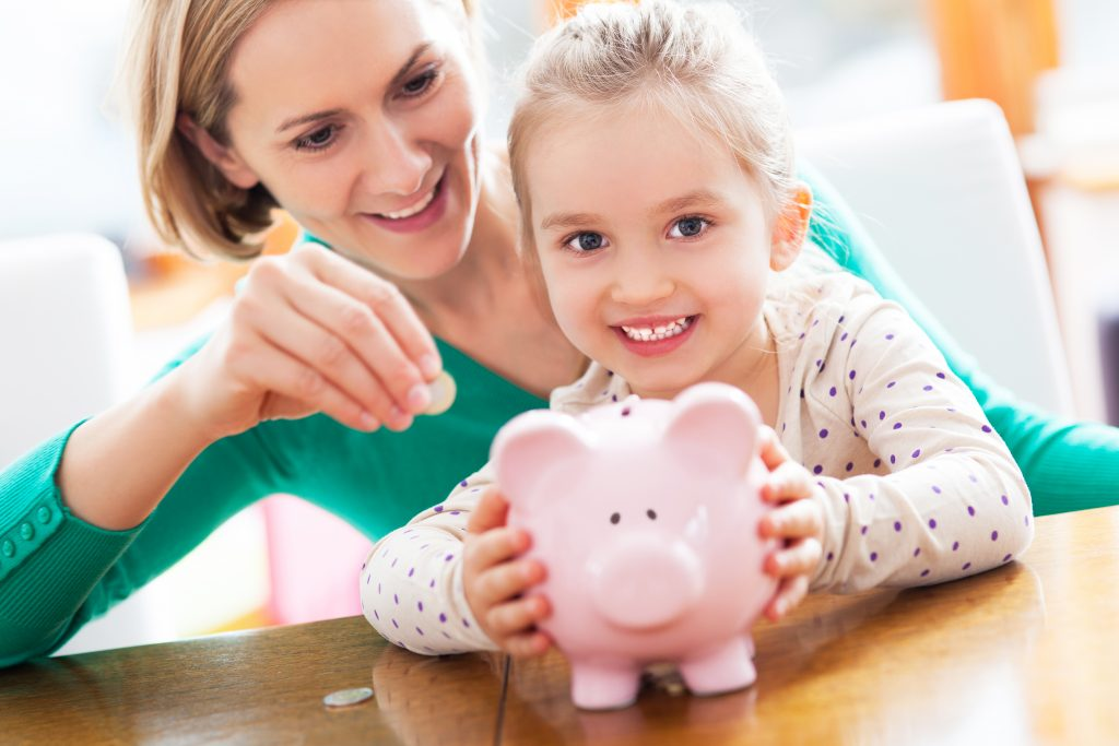 happy mother and young daughter with a piggy bank putting some money in
